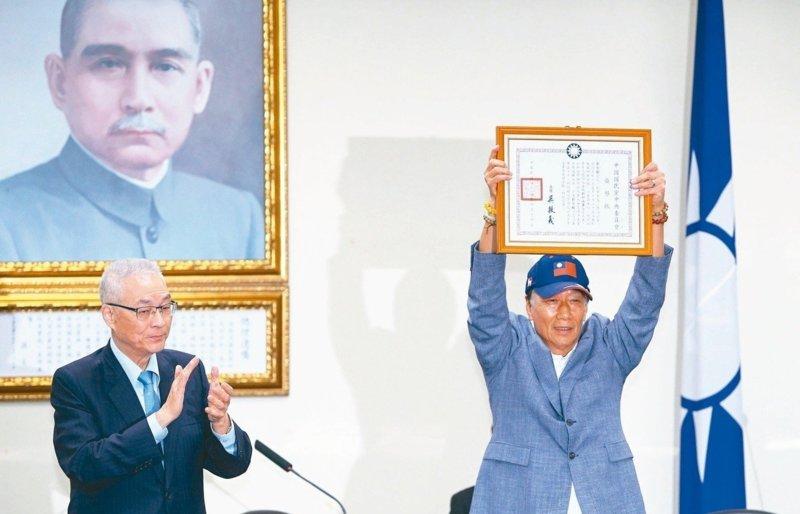 鴻海董事長郭台銘(右)從國民黨主席吳敦義手中接下榮譽狀,參加黨內總統初選資格問題順利解套。 圖/聯合報系資料照片